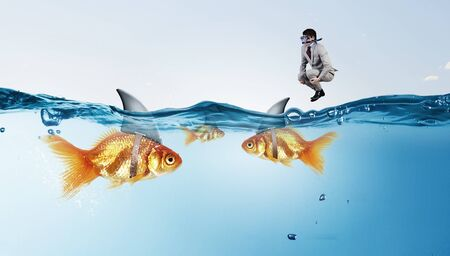 goldfish jump: Concept of fake threat when businessman jump in water with shark appear to be goldfish Stock Photo
