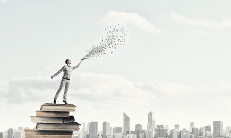 develope: Young handsome man reaching hand with book and characters flying out
