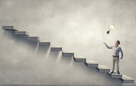 reaching hand: Young man running on steps reaching hand with book Stock Photo