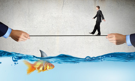 Concept of fake threat when businessman walking on rope above water with shark appear to be goldfish Reklamní fotografie