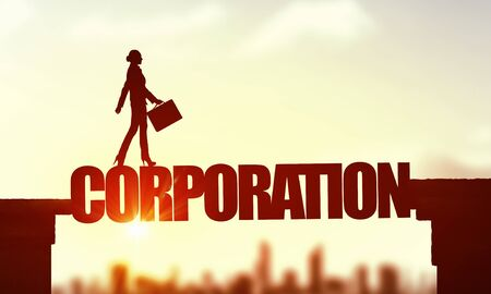Businesswoman running on corporation word bridge over precipice