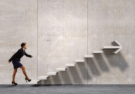 stepping stone: Businesswoman in suit stepping up stone staircase Stock Photo