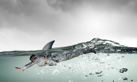 flipper: Young businessman with shark flipper swiming under water Stock Photo