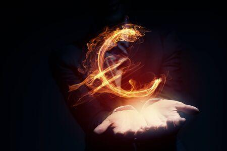 burning money: Burning euro sign in businessman palm on dark background