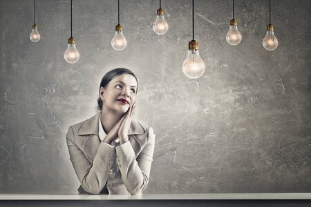 business ideas: Young businesswoman sitting at table in concrete grunge styled room and bulbs hanging from above Stock Photo