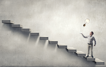 develope: Young man running on steps reaching hand with book Stock Photo