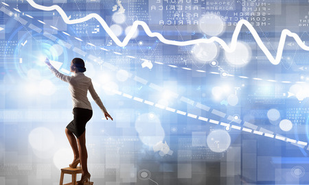 Back view of businesswoman standing on chair and reaching infographs on wall Stock Photo