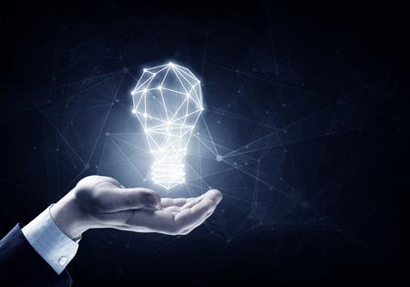 Händer av affärsman som håller upplyst glödlampe tecken Stockfoto