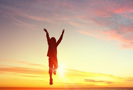 Silhouet van de jumping kid jongen over zonsondergang op de achtergrond