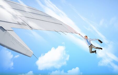 brink: Young businessman flying on edge of airplane wing Stock Photo