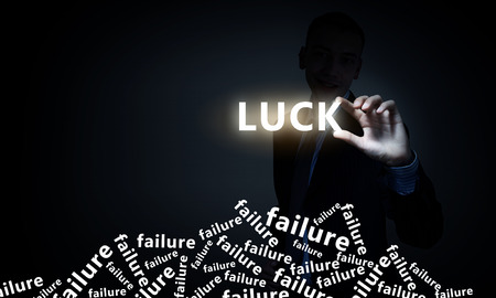 Businessman on dark background taking with fingers word luck