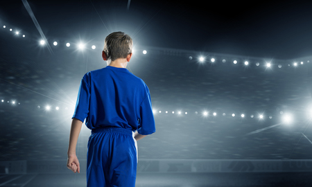 Rear view of kid boy in blue uniform on soccer stadium