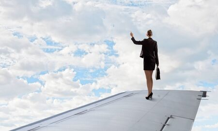 brink: Young businesswoman standing on edge of airplane wing
