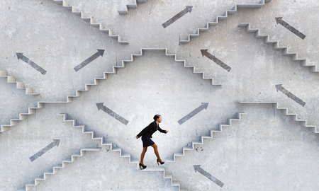 Young smiling businesswoman stepping up stone staircase Stock fotó