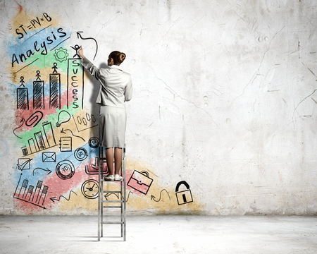 cement solution: Back view of businesswoman standing on ladder and drawing sketch on wall