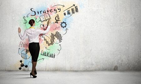 cement solution: Back view of businesswoman drawing sketch on wall Stock Photo