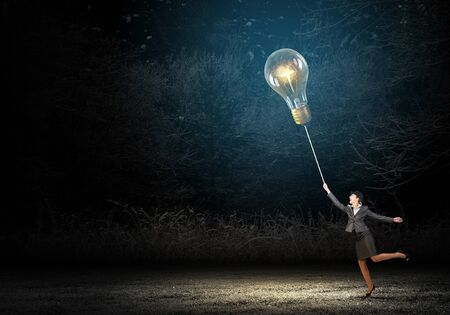 bowler: Businesswoman in bowler hat pulling rope with glass light bulb