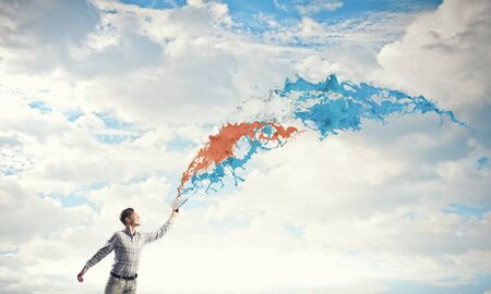 develope: Young handsome man reaching hand with book and colorful splashes flying out of pages