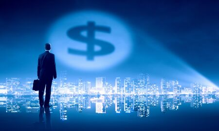 rich people: Businessman standing with back in darkness and dollar sign in spothlight Stock Photo