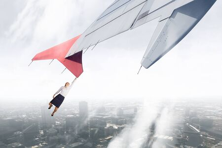 brink: Young businesswoman flying on edge of airplane wing Stock Photo