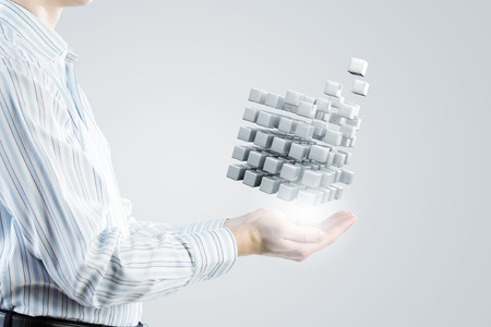 puzzling: Businessman hand shows cube as symbol of problem solving Stock Photo