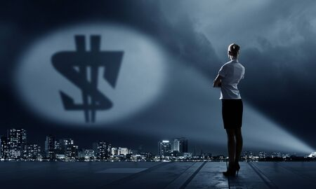 Businesswoman standing with back in darkness and dollar sign in spothlight Stock Photo