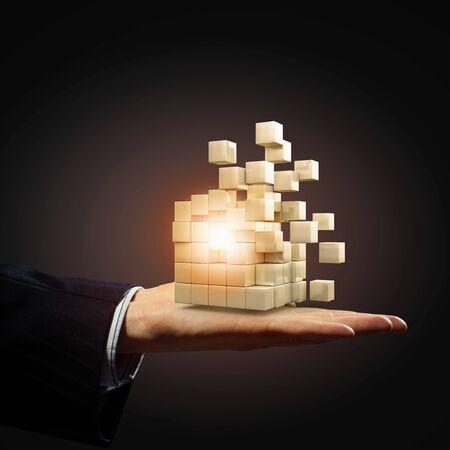 disintegrate: Businessman hand shows disintegrating cube in palm