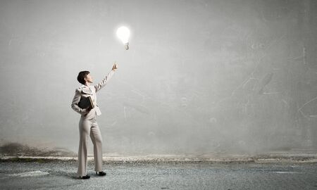 broaden: Adult woman in suit with old book in hand pointing at light bulb