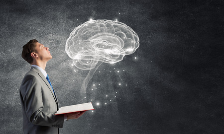 Shocked businessman holding opened book with brain picture Фото со стока