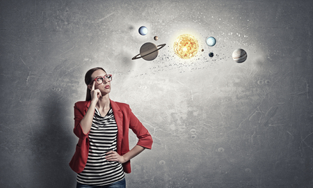 Young woman student in red jacket and glasses thinking about space Stock Photo