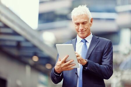 touchpad: Senior businessman holding touchpad outdoors