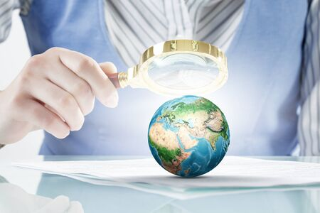 optical people person planet: Close view of businessperson exploring Earth planet with magnifying glass.   Stock Photo