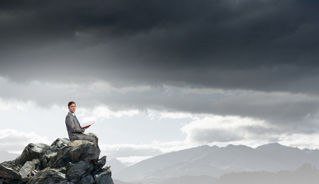 broaden: Young businessman sitting on rock top with book in hands