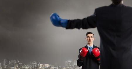 padding: Young businessman in red boxing gloves on cement background
