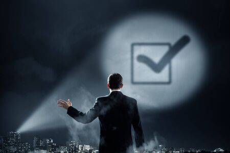 list of successful candidates: Businessman standing with back and checkbox sign in spotlight