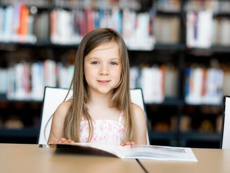intelligently: Little girl reading books in library
