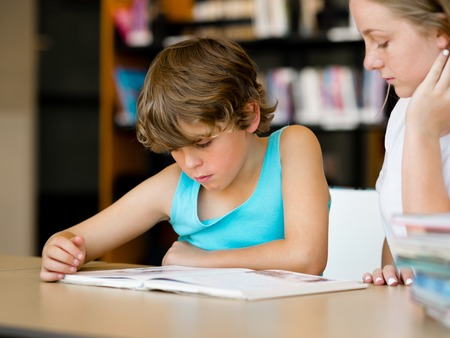 girl studying: Teenage girl  and her brother with books studying in library Stock Photo