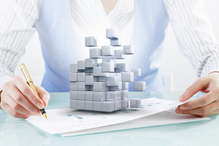 technology concept: Close up of business person writing with pen and digital cube figure on papers Stock Photo