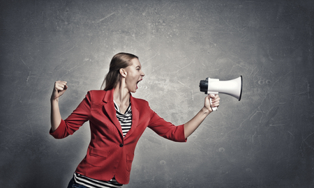 emotionally: Young woman in red jacket screaming emotionally in megaphone Stock Photo