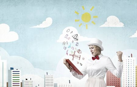 broaden: Young emotional woman in white cylinder with book in hand
