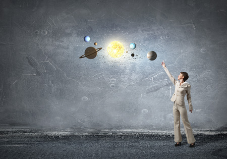 reaching hand: Young businesswoman reaching hand  to space planets Stock Photo