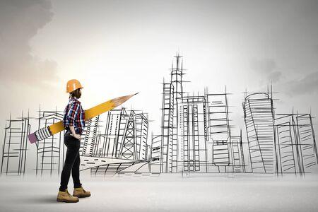 Junger weiblicher Ingenieur in Schutzhelm mit großen Bleistift und Bauten skizziert im Hintergrund Standard-Bild