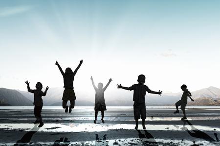 Silhouetten van groep kinderen hoog springen met vreugde op de zonsondergang op de achtergrond Stockfoto