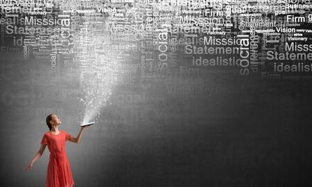 broaden: Young woman in red dress with opened book in hand Stock Photo