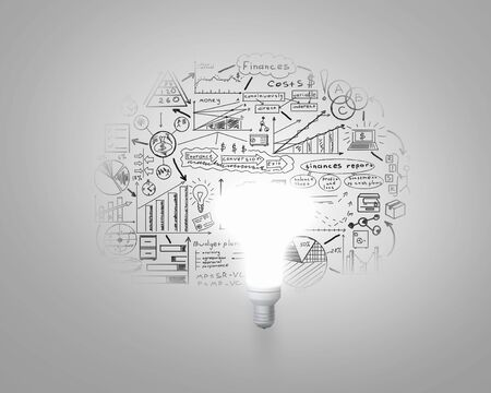 Glowing light bulb on wall with sketches strategy plan