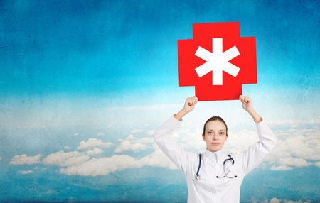 healthcare facility: Attractive female doctor in white showing medicine cross sign