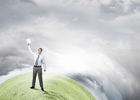 reaching hand: Young screaming businessman on hill reaching hand with opened book Stock Photo
