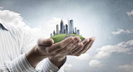 city buildings: Close up of hands holding image of modern cityscape