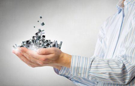 Pile of laptops in human hands as technology concept