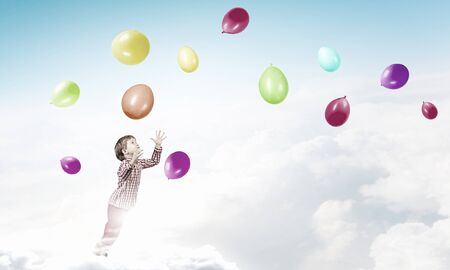 joyfully: Little cute boy playing joyfully with colorful balloon